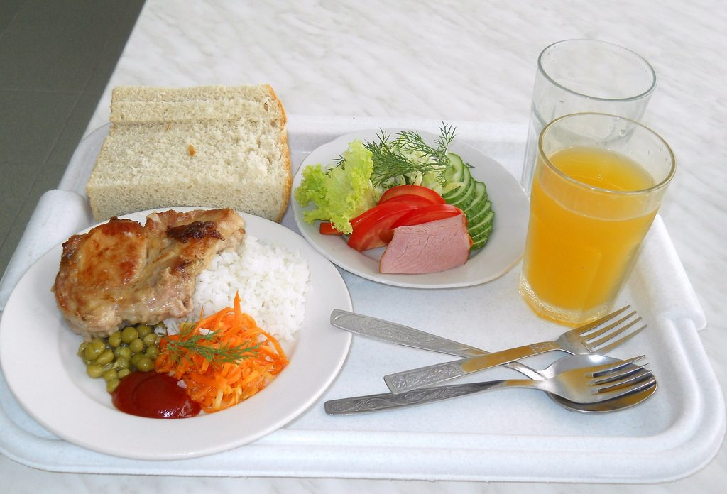 food tray with bread, orange juice and rice with meat and vegetables