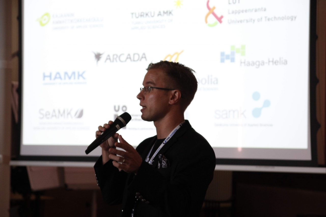 co-founder of Edunation giving a welcome speech, holding a microphone