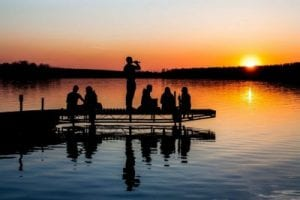 Students sitting on a deck looking at sunset near lake in Finland, Europe