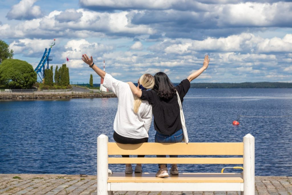 Two girls in Finland hugging and watching the lake