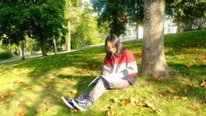 Foreign student reading a book inautumn