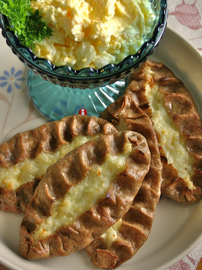 Finnish Karelian pie on a plate with glass cup of yellow egg butter