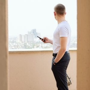 man holding phone looking at the view