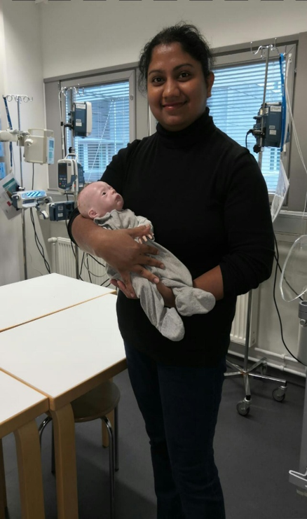 Foreign student holding a baby mannequin