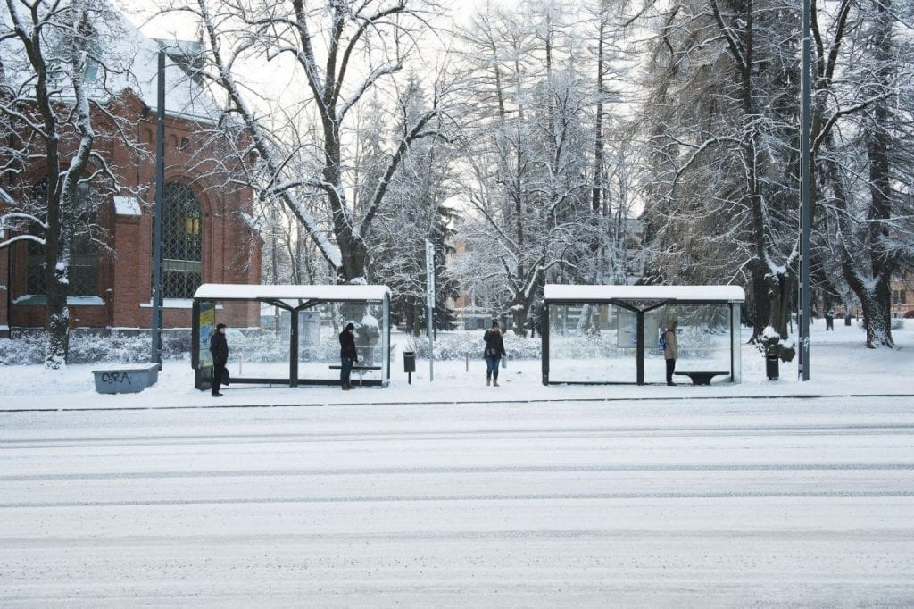 Bus stop with few people and personal space, winter season.