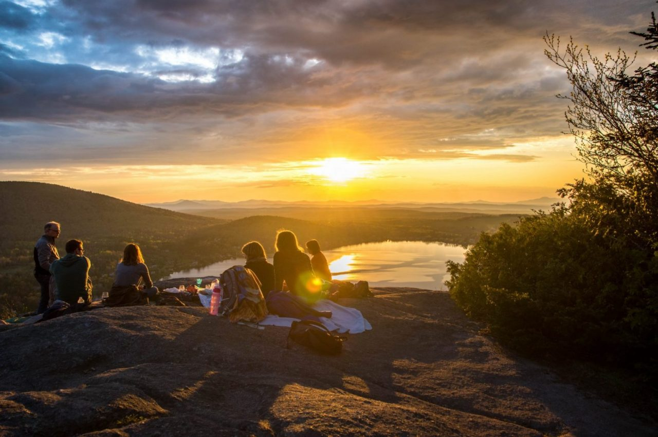 Group of people having a picnic, sunset view