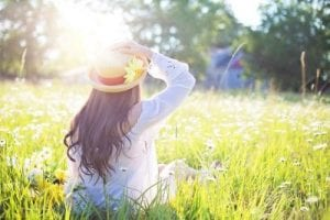 Woman sitting in a field sunny day