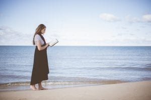A girl reading a book by the ocean