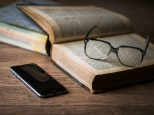A phone next to an open book that has glasses on top.