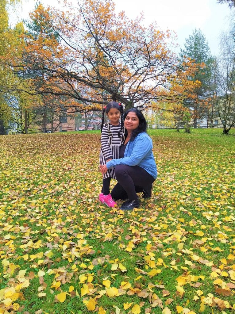 Mother and daughter at a park with autumn leaves