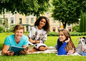 One male and two female students studying at a park