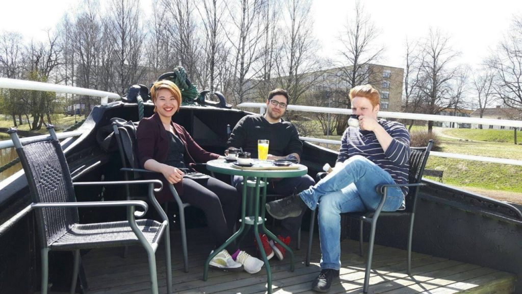 Three students drinking coffee and sitting in a table outside