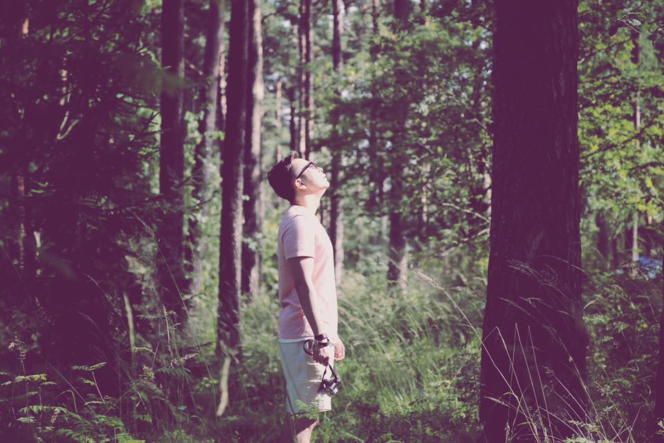 boy standing alone and holding a camera in a forest