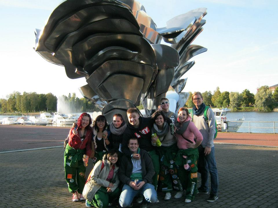 Group of students posing in front of a statue