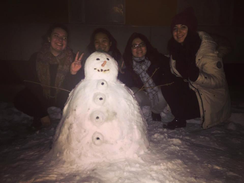 group of international friends around a snowman in Finland