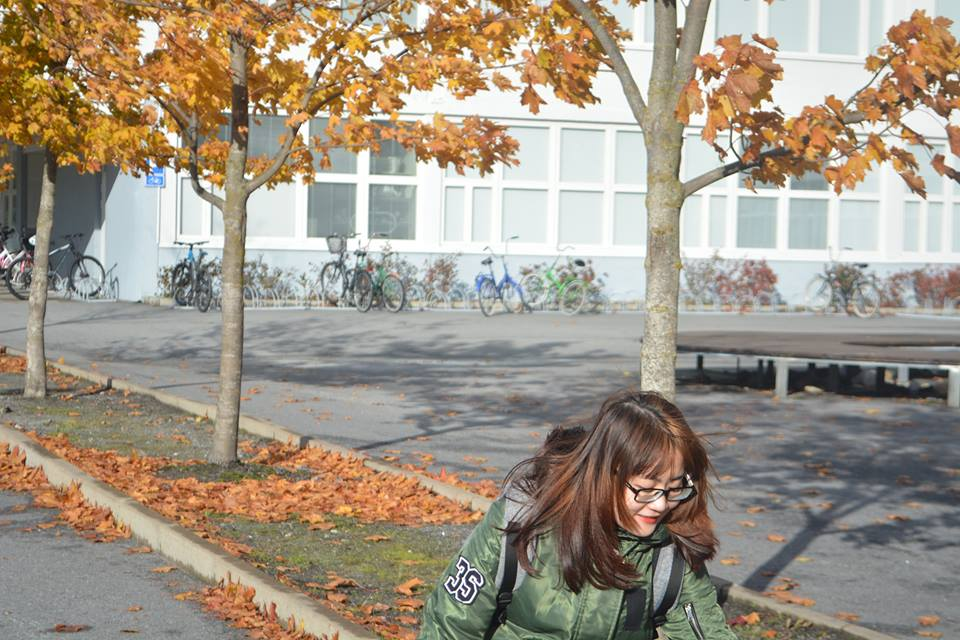 vietnamese girl on a street in front of a school in Finland in autumn