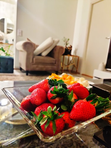 Fresh strawberries in a salad bowl overlooking couch