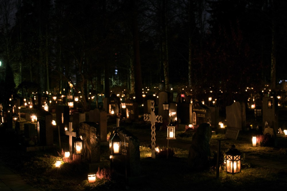 Graveyard at night in Finland with a sea of lit candles