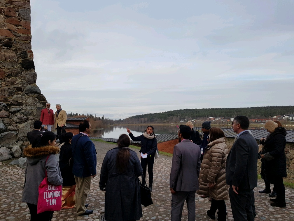 People standing outside a medieval castle listening to a presentation in Finland