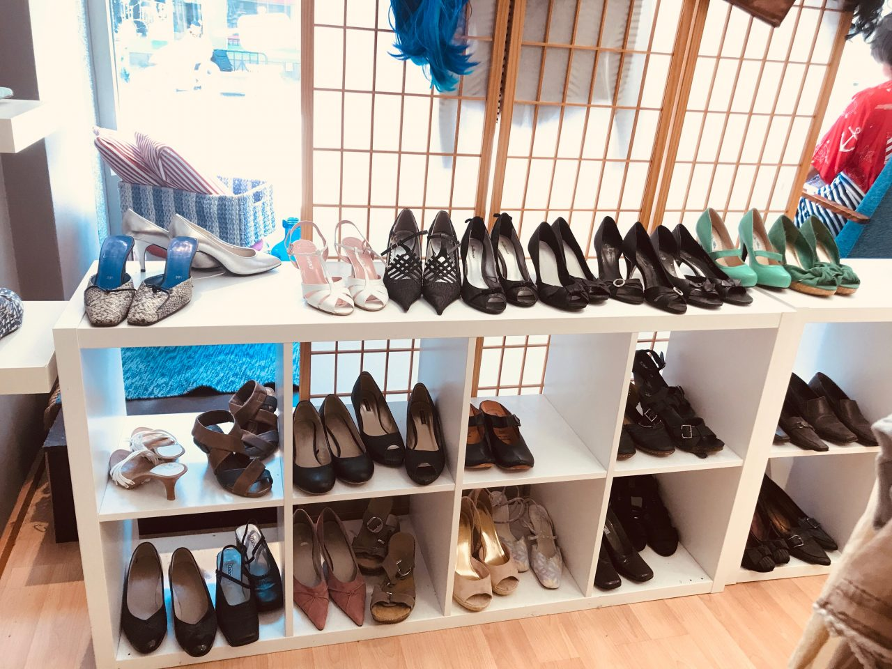 Many pairs of shoes on a shoe rack