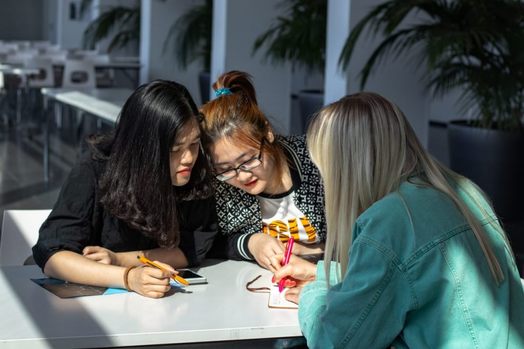 three international students working together around a table in Finland