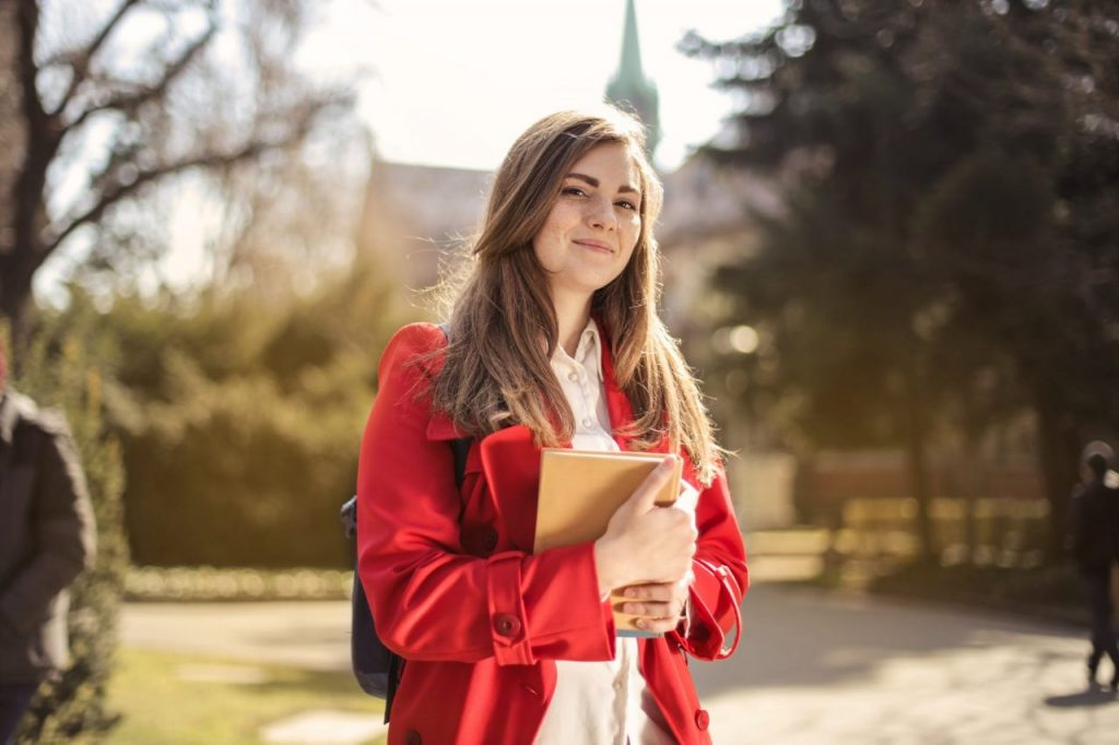 A student in a red jacket holding a book