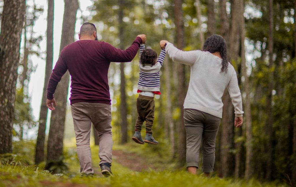 Two parents and a child walking through the forest