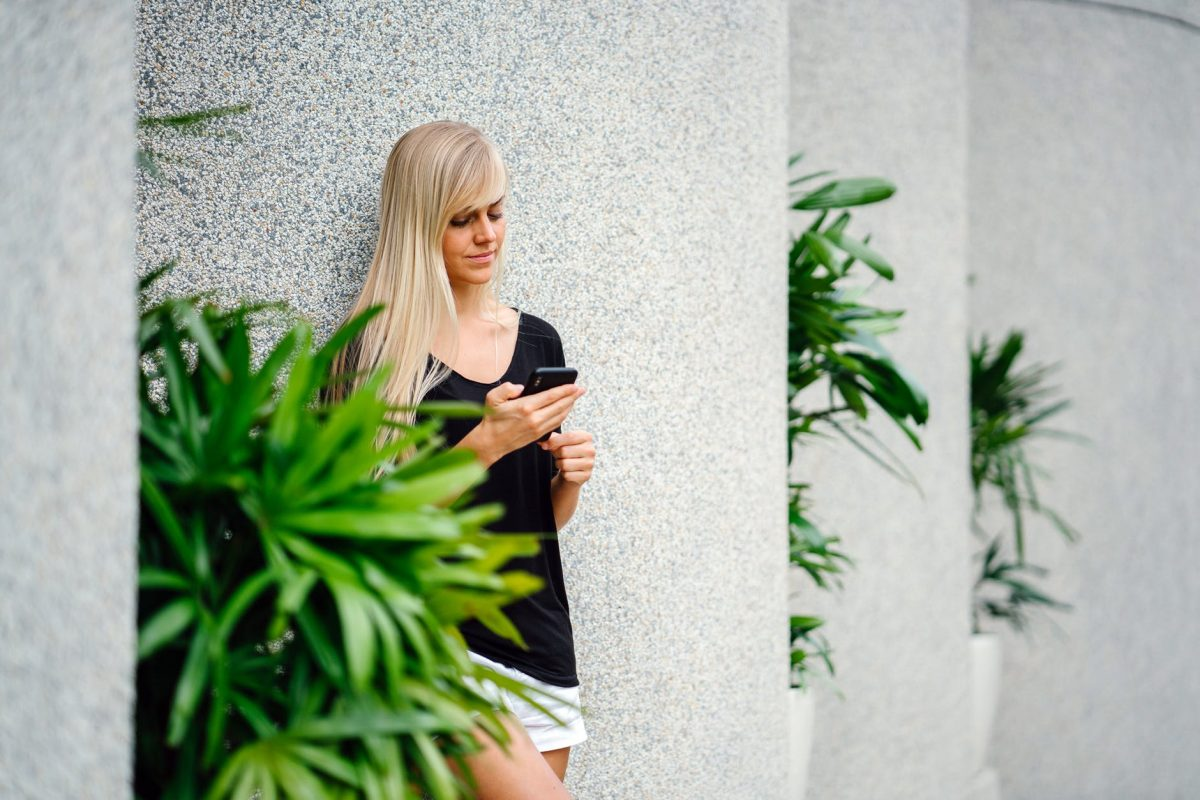 student leaning against a wall on her phone