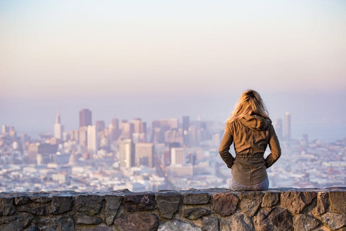 student sitting on a stone wall overlooking the city