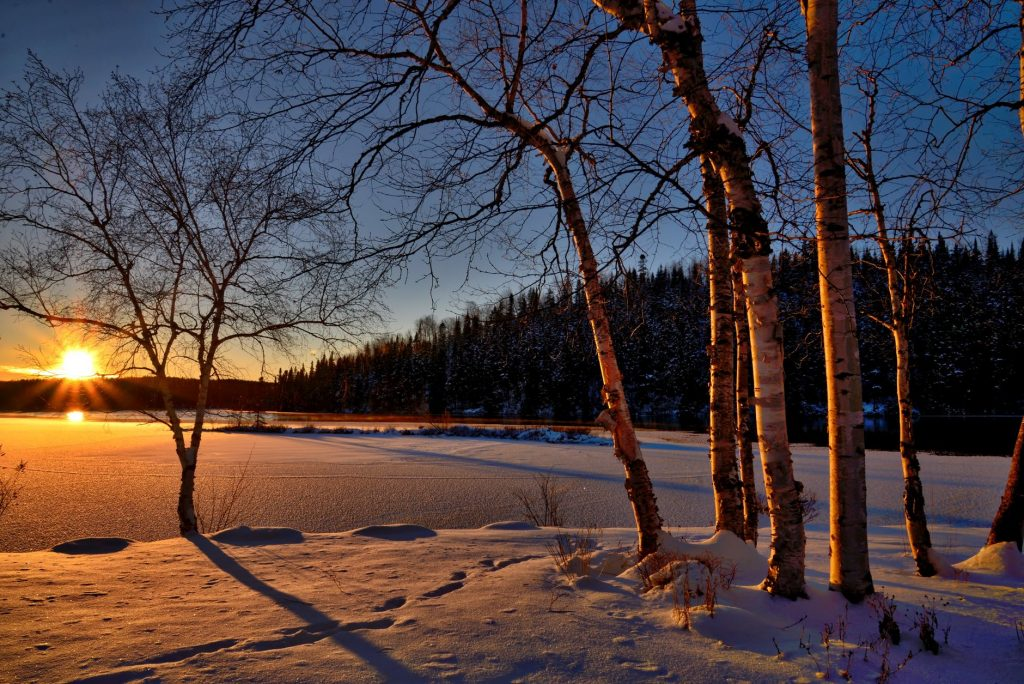 Sunset during winter season, snow covering the lake in Finland
