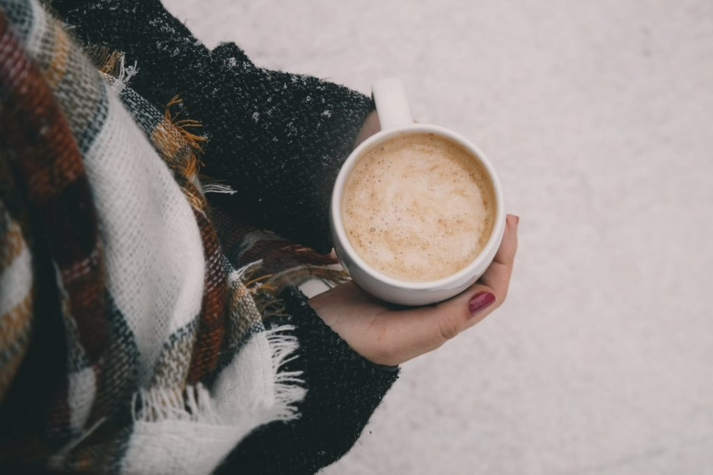 Woman with scarf holding coffee in hand