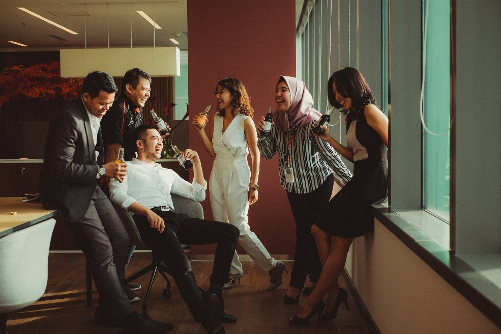 international group of young people having a drink and laughing together at an office
