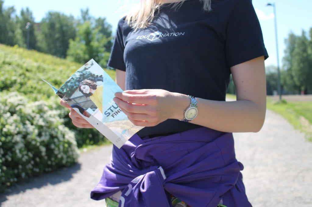 Pinja holding a brochure outside