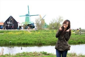 Vietnamese student posing for a picture with green scenery background