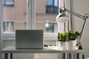 White laptop, a lamp and some plants on a desk in Finland