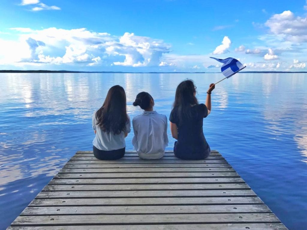 Students sitting by the lake finnish flag